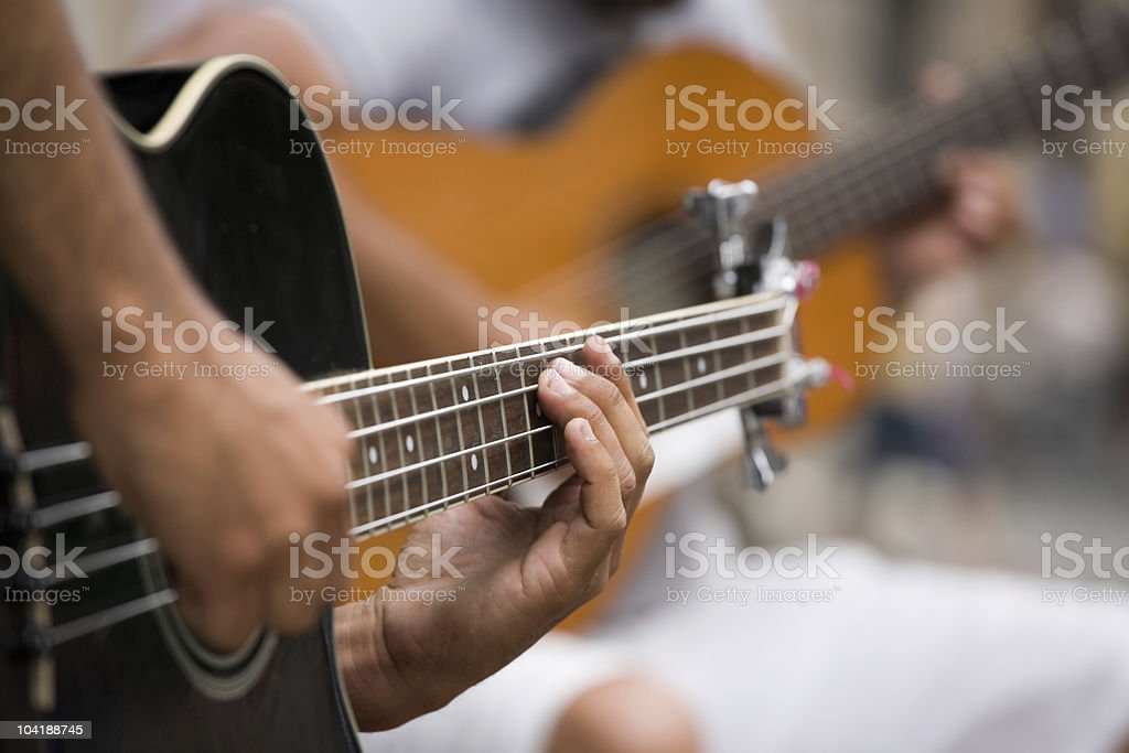 Closeup of a guitar player and his instrument stock photo