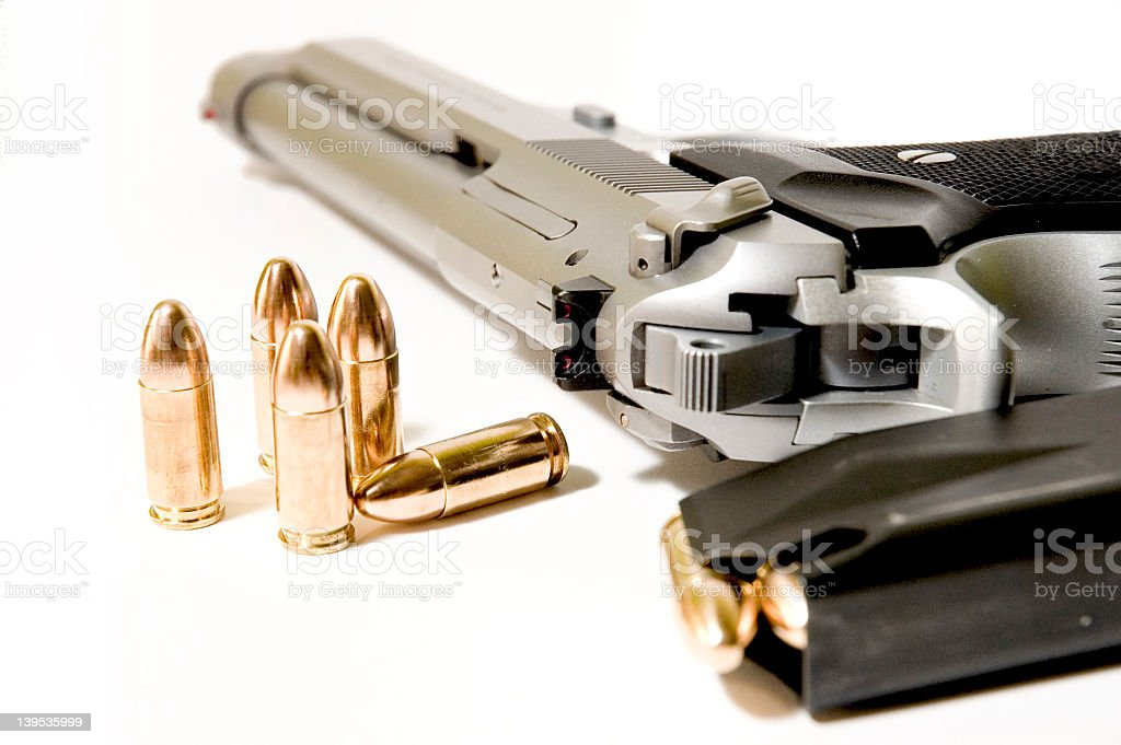 Close-up of a gun next to full clip with five single bullets royalty-free stock photo
