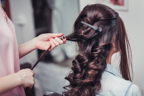 Closeup of a hairdresser coiffeur makes beauty hairstyle. Closeup of a hairdresser coiffeur makes beauty hairstyle. saloon stock pictures, royalty-free photos & images