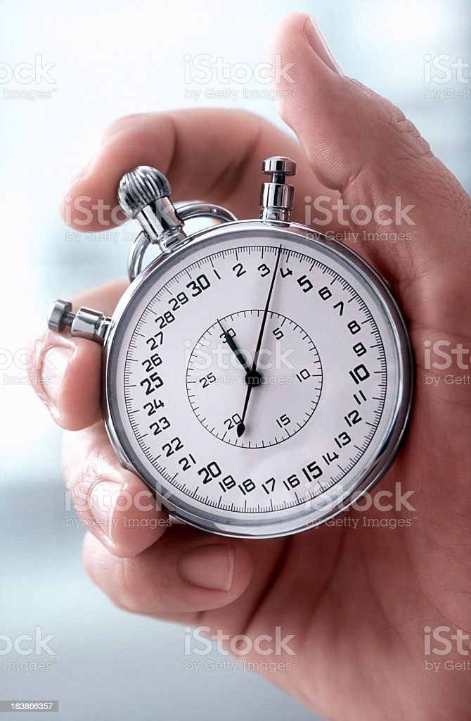 Close-up of a hand holding a classic silver stopwatch royalty-free stock photo