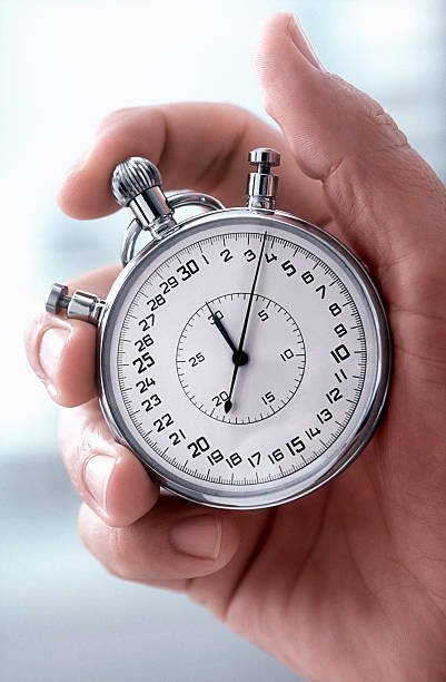 Close-up of a hand holding a classic silver stopwatch stock photo