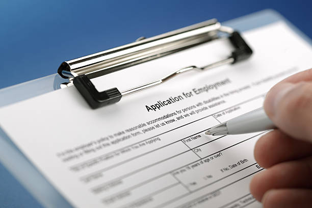 Close-up of a hand holding a pen to an employee application Completing an employment application form application form stock pictures, royalty-free photos & images