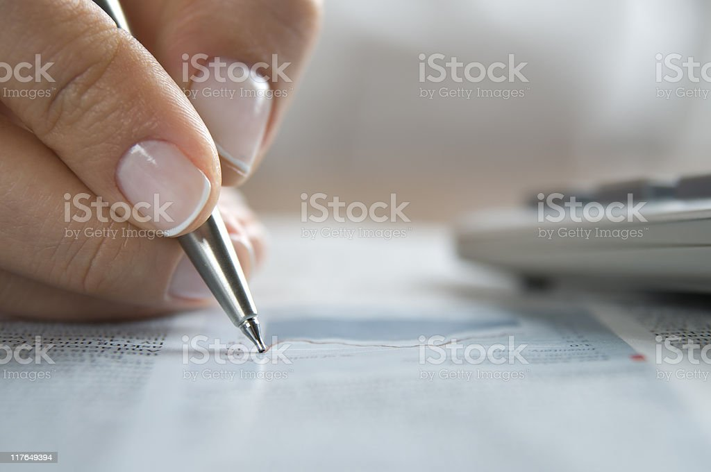 Close-up of a hand writing with a pen with calculator near royalty-free stock photo