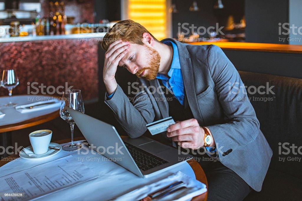 Close-up de um bonito jovem empresário segurando um cartão de crédito em um café / restaurante - Foto de stock de 30 Anos royalty-free