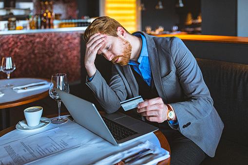 Foto de Closeup De Um Bonito Jovem Empresário Segurando Um Cartão De Crédito Em Um Café Restaurante e mais fotos de stock de 30 Anos
