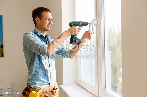 966792200 istock photo Close-up of a handyman fixing window frame 1186967178