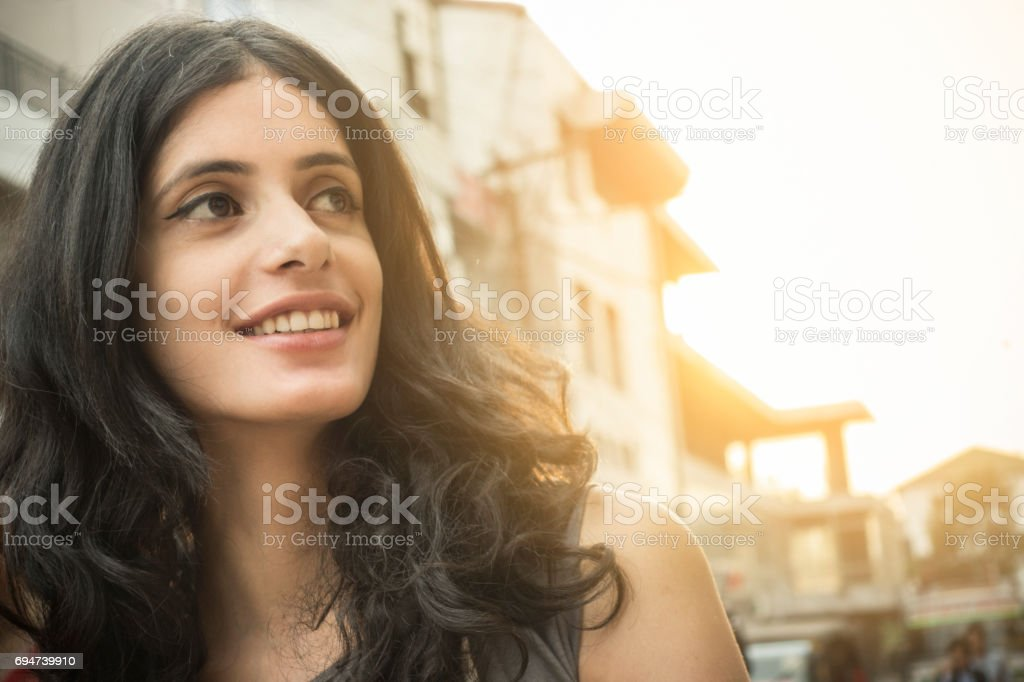 Close-up of a happy Asian girl on city street. stock photo