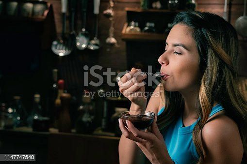 Close-up of a happy Hispanic woman eating indulgence chocolate mousse a rustic kitchen