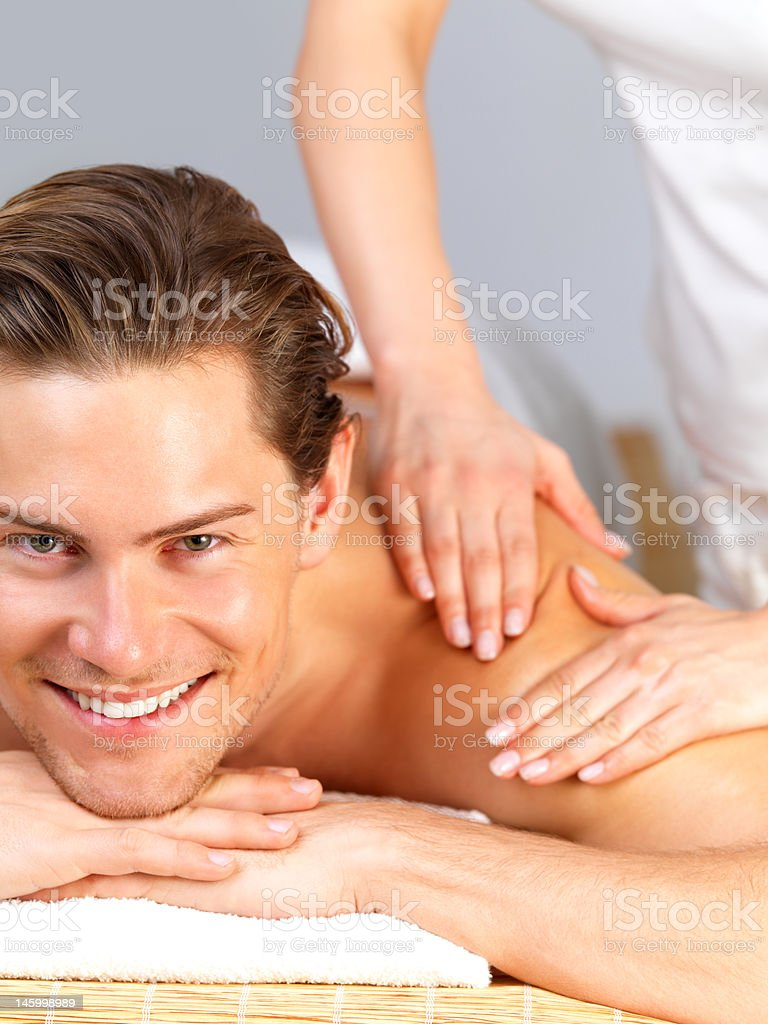 Close-up of a happy young man receiving shoulder massage royalty-free stock photo