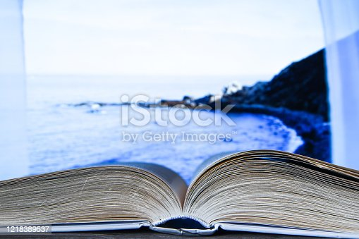 1034955096 istock photo Closeup of a hardcover book open in the middle, Open book, window beach sea vacation background 1218389537