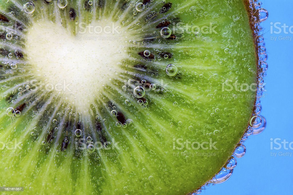Closeup of a heart shaped kiwi slice in water bubbles royalty-free stock photo