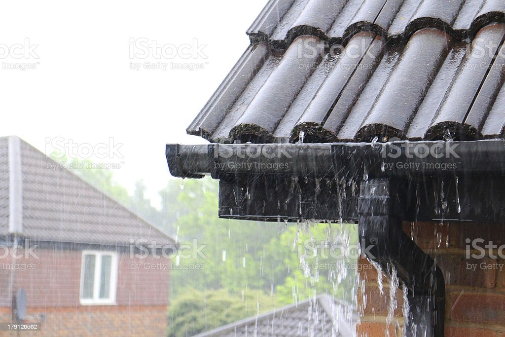 A close-up of a house's gutters during a rain stock photo