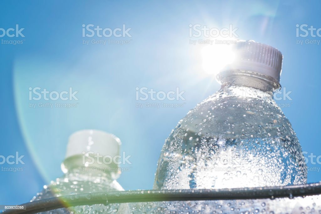 Close-up of a Ice cold water bottle in a bucket on a hot Summer day stock photo