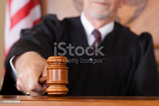 A close-up of a judge's gavel in his hand in the courtroom.