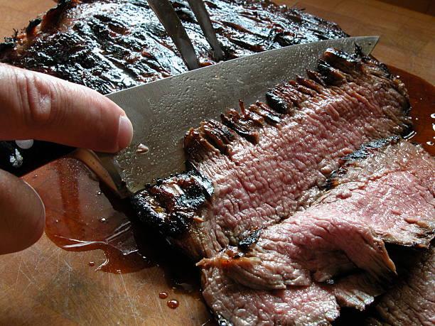 Close-up of a knife carving a piece of grilled flank stake stock photo