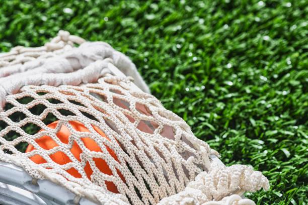a close-up of a lacrosse stick netting covering an orange ball - kij do gry w lacrosse zdjęcia i obrazy z banku zdjęć