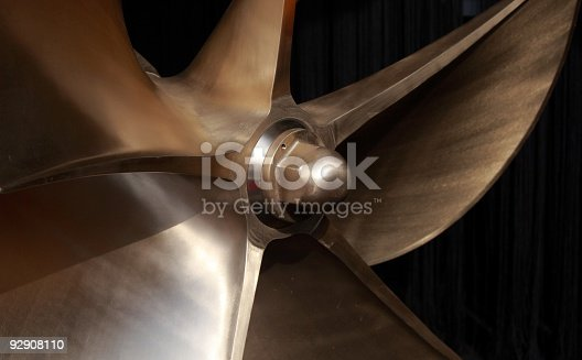 brand new Large polished brass boat propeller with 6 blades. Depth of field with focal point on very center.
