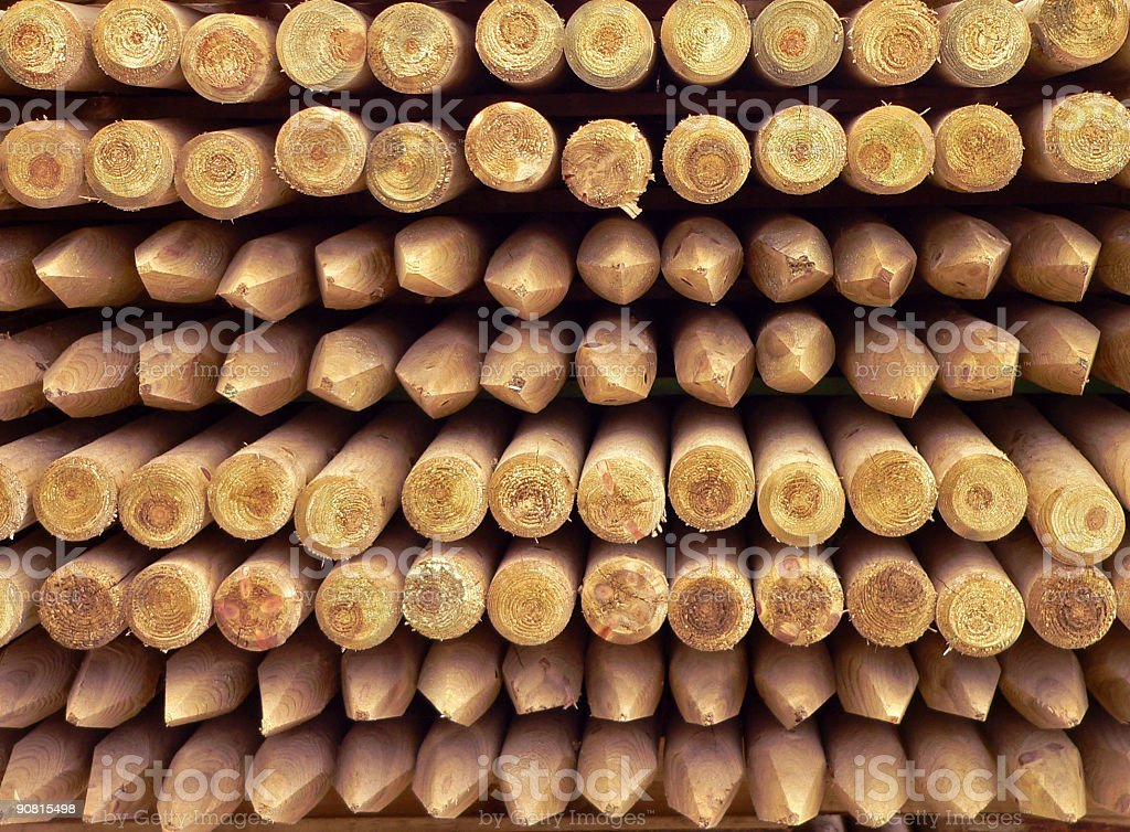 A close-up of a large stack of wooden poles royalty-free stock photo