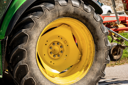 Close-up of a large yellow wheel of a tractor with black tire, agricultural machinery