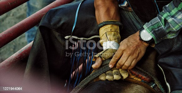 Close-Up of a Latino Bull Rider's Hands Adjusting His Grip on the Rope while Sitting Atop a Bull before Competing in a Bull Riding Event