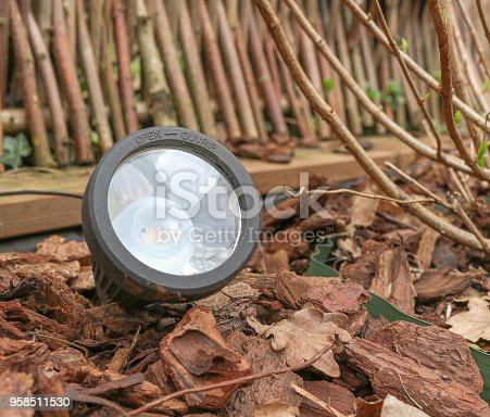 Closeup of a LED garden lamp, stuck in a flowerbed and between bark mulch of pine trees. Bulb of the modern lamp can be seen through the glass front. Lamp is powered by a solar module