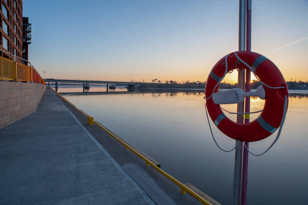 A closeup of a lifebuoy during beautiful winter sunrise in the urban waterfront. stock photo