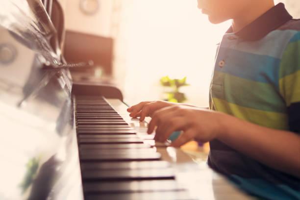 nahaufnahme eines kleinen jungen, klavier zu spielen - sanft und sorgfältig stock-fotos und bilder