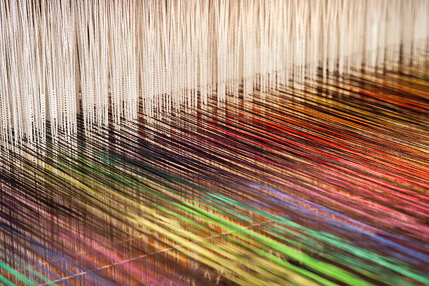 Close-up of a loom weaving colorful fabric (XXXL) Close-up of a loom weaving colorful fabric (XXXL) threading stock pictures, royalty-free photos & images