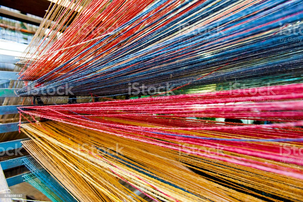 Close-up of a loom weaving colorful fabric stock photo