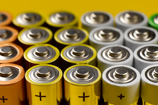 Closeup of a lot of color AA batteries on a bright yellow background.