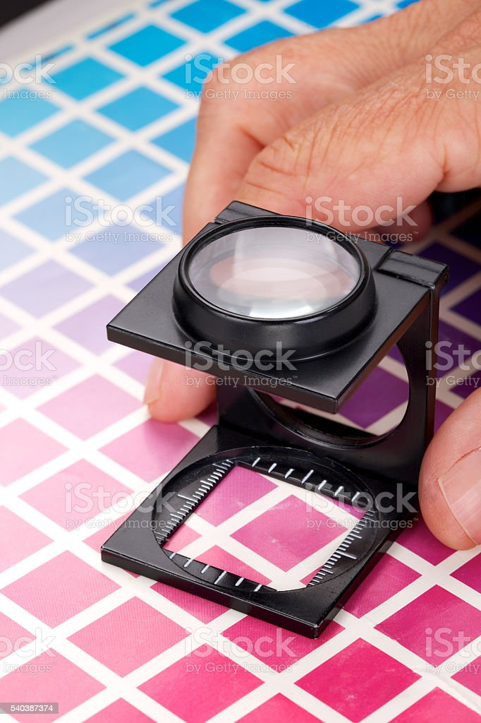 Close-up of a loupe and hand on CMYK color scales stock photo