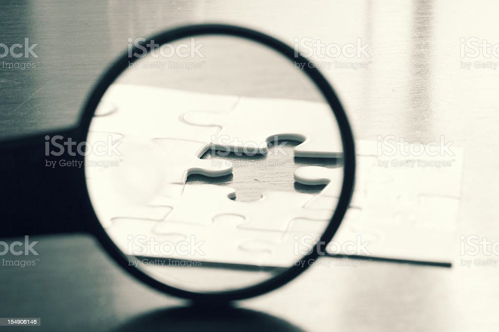 Close-up of a magnifying glass focused on a puzzle stock photo