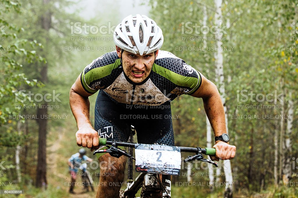 closeup of a male cyclist rides through forest stock photo