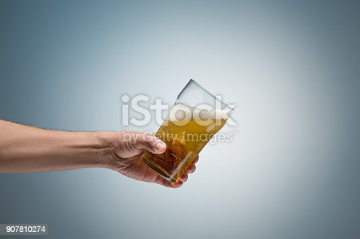 Closeup of a male hand holding up a glass of beer over a blue background