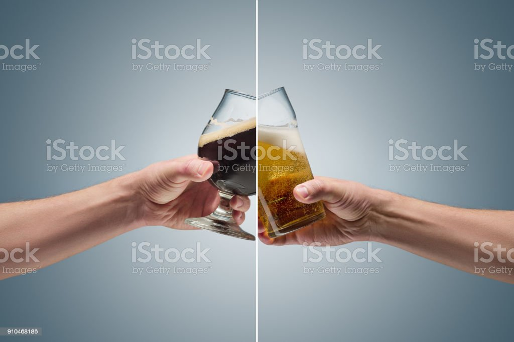 Closeup of a male hand holding up a glass of beer stock photo