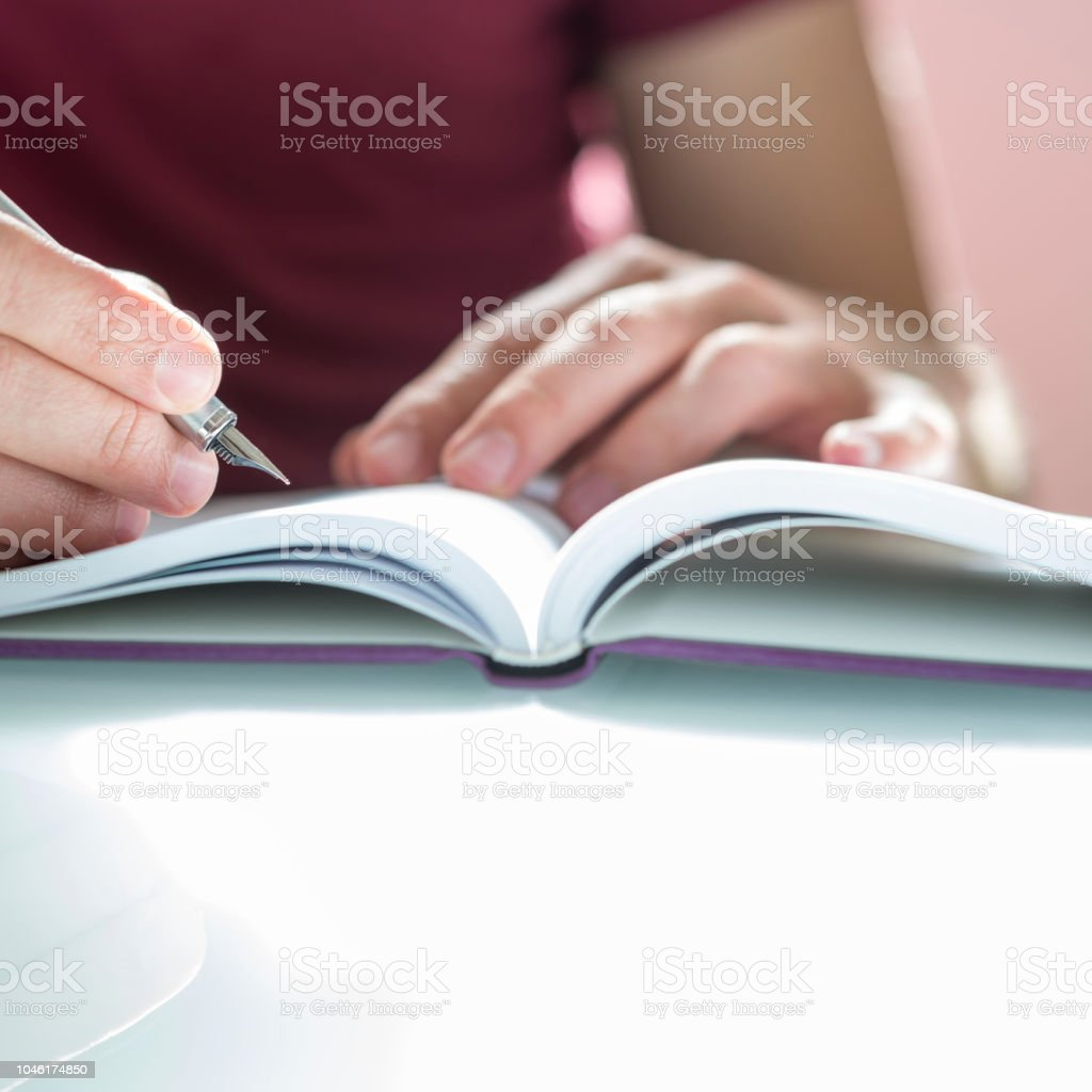 Closeup of a male hand writing on notepad with silver pen stock photo