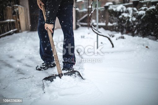 Senior adult man cleaning his driveway and car after a heavy snowfall