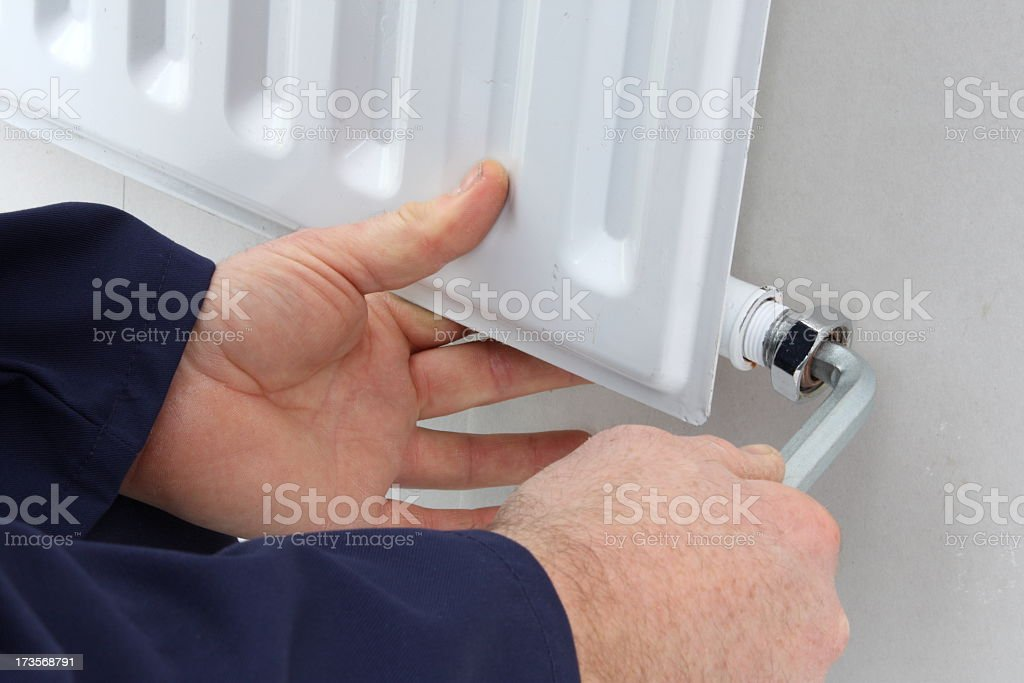 Close-up of a man doing repair work on a radiator royalty-free stock photo