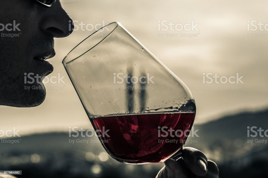 Closeup of a man face drinking red wine with a dirty wine glass in a...