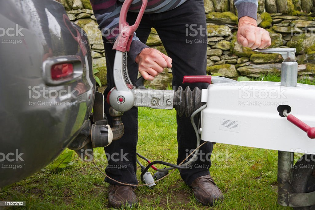 Close-up of a man hooking up a trailer to a car stock photo