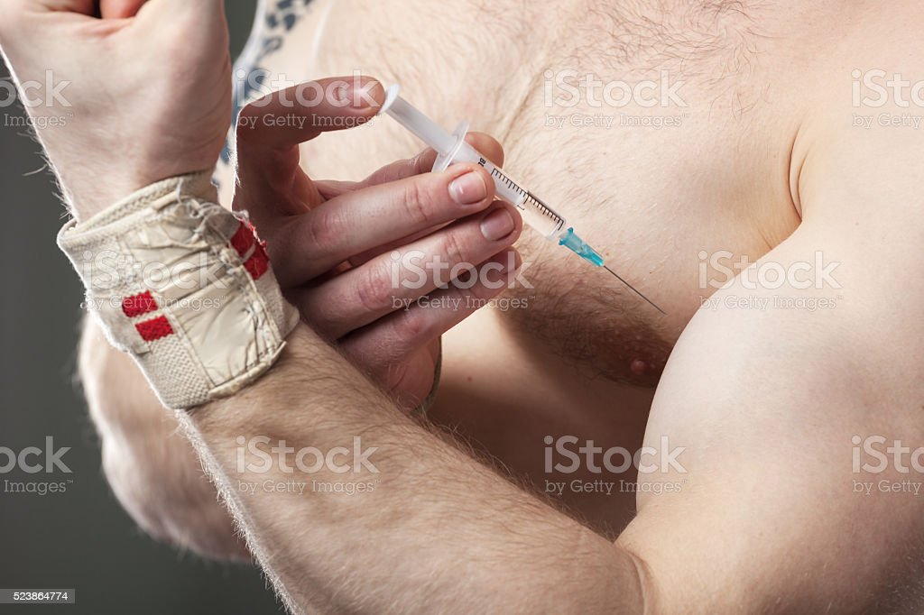 Closeup of a man injecting himself with steroids. Close up of a muscular man injecting himself with steroids. Adult Stock Photo