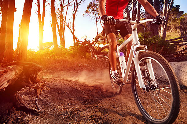 Close-up of a man on mountain bike riding on trail Mountain Bike cyclist riding single track at sunrise healthy lifestyle active athlete doing sport mountain biking stock pictures, royalty-free photos & images