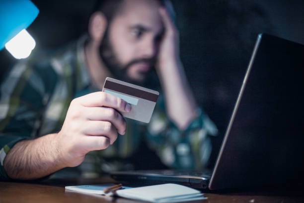 Close-up of a man paying bills from home by using a laptop and a credit card stock photo