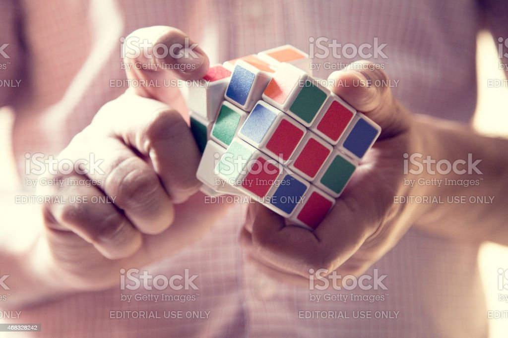 Close-up of a man playing puzzle cube stock photo