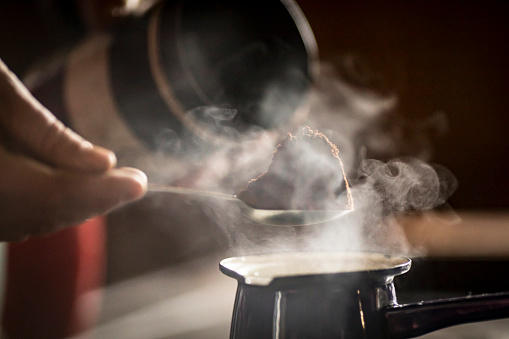 Close-up of a Man Preparing Coffee in Coffee Pot on Stove.