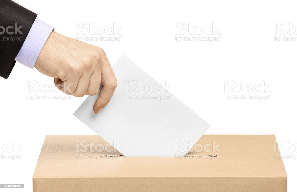 A close-up of a man putting a voting ballot in a box royalty-free stock photo