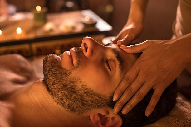 Close-up of a man receiving facial massage at the spa. stock photo