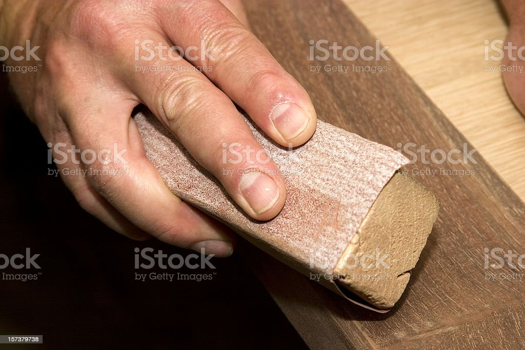 Close-up of a man sanding by hand in the workshop stock photo