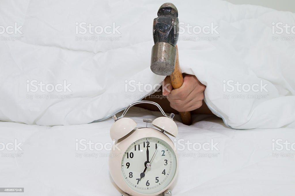 Closeup of a man with a hammer smashing alarm clock stock photo