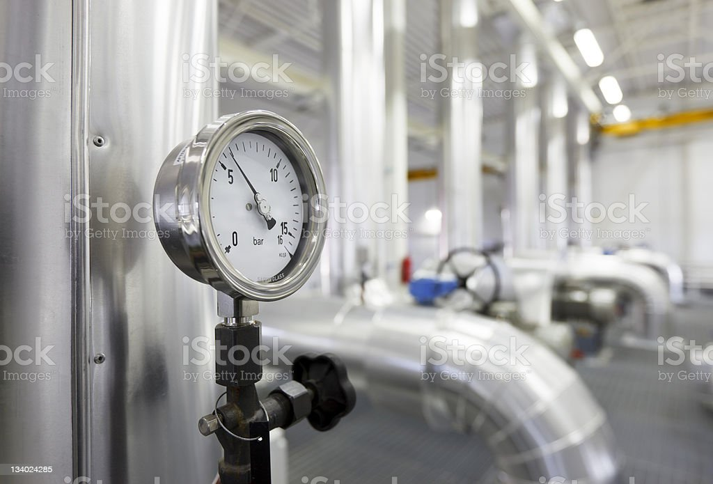 A close-up of a manometer on a vertical pipe in a building stock photo